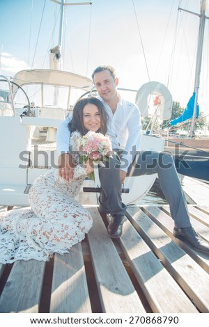 Attractive beautiful couple sitting on the ground  near yachts. - stock photo