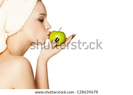 attractive beautiful girl with a towel on her head kisses a green apple
