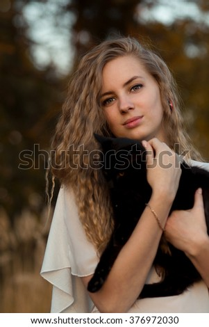 Attractive,beautiful,pretty,lovely,stunning,snorting,nice,adorable girl with black cat.Very beautiful girl hold cute cat,black cat.Attractive woman,model,blonde girl with long hair and lovely cat,cat. - stock photo