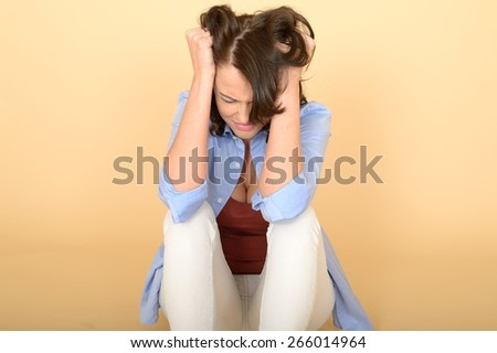 Attractive Beautiful Sad Depressed and Angry Young Woman Sitting on the Floor Wearing a Blue Shirt and White Jeans  - stock photo