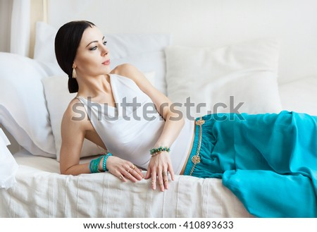 Attractive beautiful tanned woman in oriental jewelry is lying on a white bed. She a elate and beautiful. She is an oriental princess. Morocco. White room, bright and hot sunny summer day.