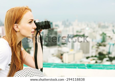 Attractive beautiful woman photographer take a pictures outdoors in Bangkok city travel from the top of skyscraper  - stock photo