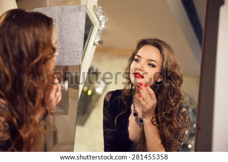 Attractive beautiful young girl model looking in mirror at herself. Makeup. Red lips. Long wavy hair style. Charming female. - stock photo