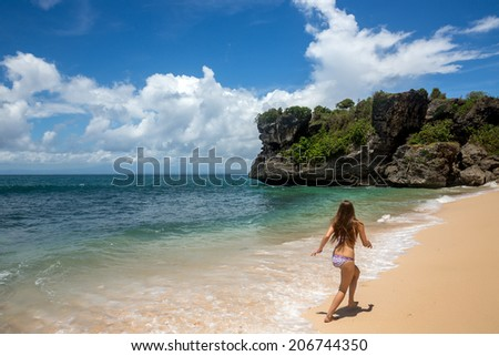 Attractive beautiful young woman in swimsuit running along shore of ocean in hot summer day