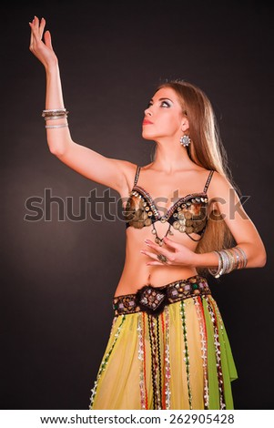 Attractive bellydancer with long haired girl in green dress performing a dance tribl