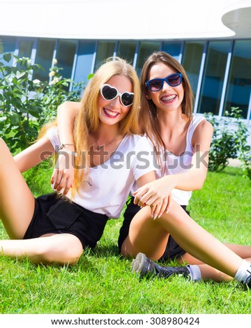 Attractive best friends having fun in city park. Hipster Girls Laughing and having fun on summer holidays and vacation-girls going crazy on the grass.Wearing similar outfit.Fun,joy,playful mood.  - stock photo