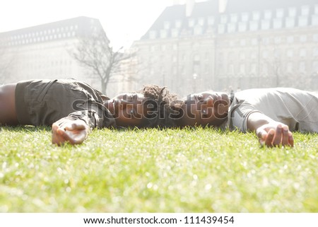 Attractive black couple laying down on green grass head to head, while visiting London city on vacations.