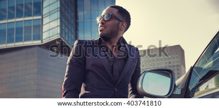 Attractive black man in a suit posing near car in town center.