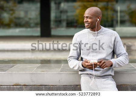Attractive black man listening to music with headphones in urban background. Male in sportswear outdoors.