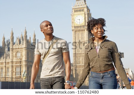 Attractive black tourist couple holding hands and walking past Big Ben while visiting London city on vacation. - stock photo