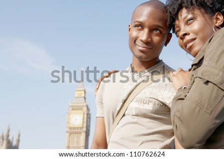Attractive black tourist couple standing by Big Ben while visiting London city on vacation, smiling.