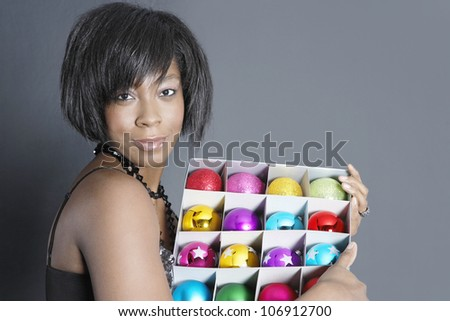 Attractive black woman holding a box of Christmas barballs and smiling at camera.