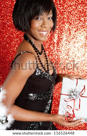 Attractive black woman holding a gift box while smiling against a red glitter background at a Christmas party. - stock photo