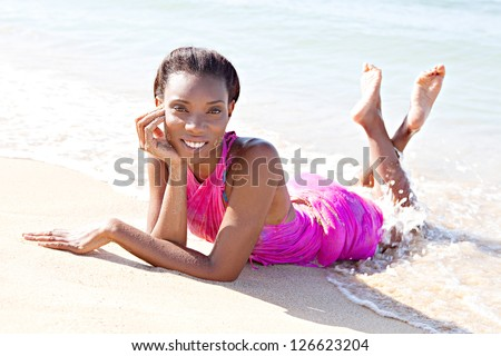 Attractive black woman laying down on the sea shore with the waves bathing her under the sun while on a tropical vacation. - stock photo