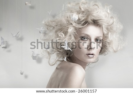 Attractive blond beauty with origami in the background - stock photo