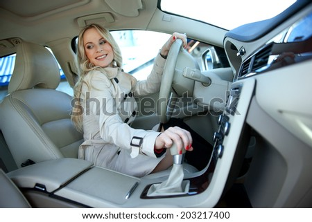 attractive blond business woman in driver seat of the car - stock photo