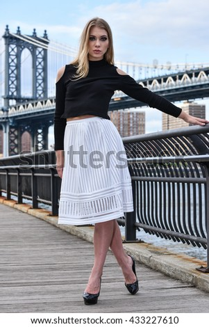 Attractive blond fashion model posing pretty on the pier with Manhattan Bridge on the background, New York City.
