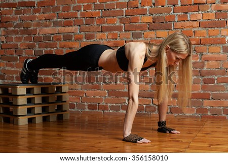 Attractive blond fitness model performing push ups with a box at the gym - stock photo