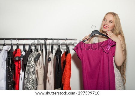 Attractive blond girl is choosing clothing for date. She took one dress from the rack. The lady is smiling and looking happily aside. Isolated on background - stock photo