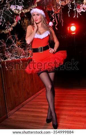 attractive blond girl posing in red minidress as sexy santa helper