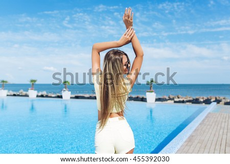 Attractive blond girl with long hair is standing near pool. She wears yellow short shorts,T-shirt, sunglasses. She holds her hands above. View from back. - stock photo