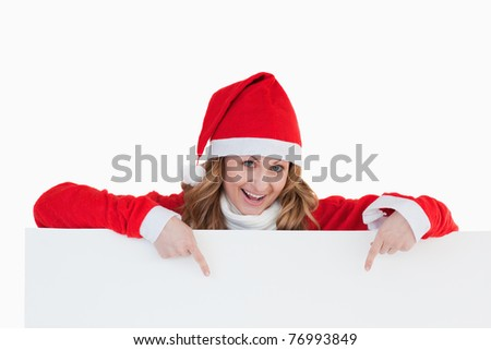 Attractive blond-haired woman dressed as Santa Claus holding a white board while showing something