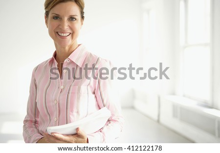 Attractive blond mature business woman in her office - stock photo