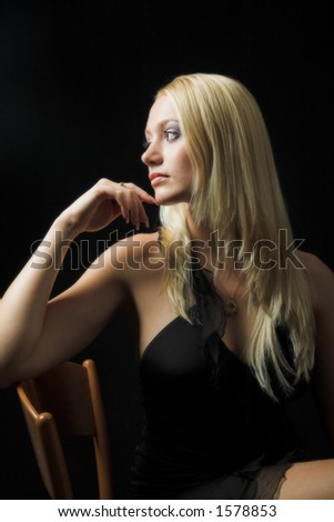 Attractive blond model on black background - sexy black dress - very high resolution - sitting on the chair - stock photo