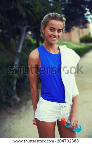 Attractive blond runner with beautiful figure smiling standing in the beautiful green park, evening run, fitness and healthy lifestyle concept