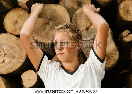 Attractive blond teenage boy with a pensive expression leaning back against a stack of logs with his arms raised staring into the distance