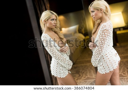 Attractive blond woman by the mirror - stock photo