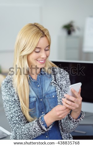 Attractive blond woman checking for messages on her mobile phone with a pleased smile, close up upper body view indoors - stock photo