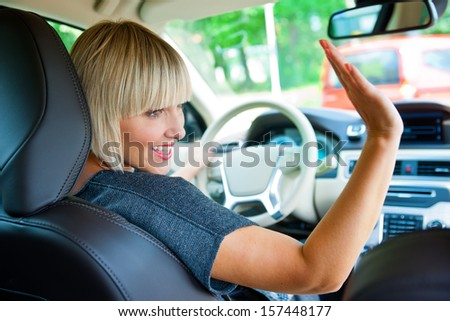 attractive blond woman drives her car and waiving