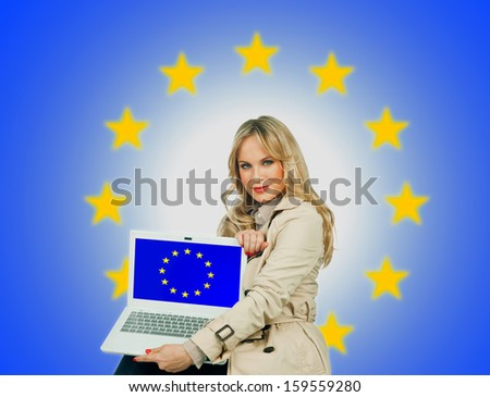 attractive blond woman holding laptop with european union flag on the screen  - stock photo