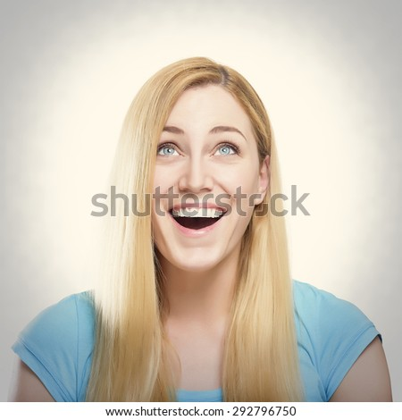 Attractive blond woman in a blue shirt, smiling and looking up. Toned photo. - stock photo