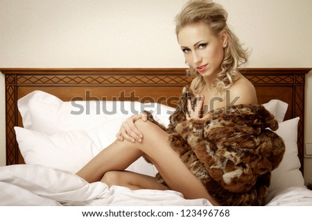 attractive blond woman in elegant fashiontable brown fur lie on the bed