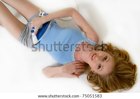 Attractive blond woman lying on the floor with a clothing iron on stomach as if ironing it to make it flat