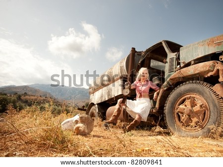 Attractive blond woman near an old truck. - stock photo