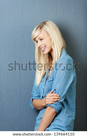 Attractive blond woman smiling while looking at something - stock photo