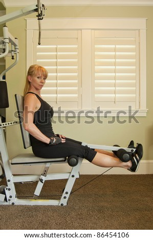 Attractive blond woman using exercise machine for leg lifts