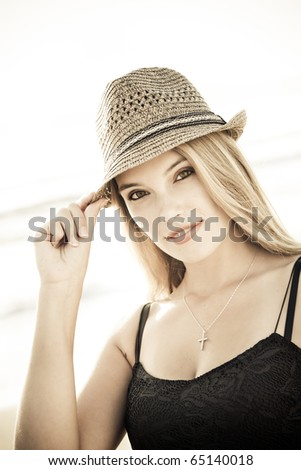 Attractive blond woman wearing a straw hat on the beach. - stock photo