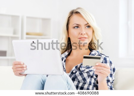 Attractive blond woman with a credit card and a tablet computer.  - stock photo