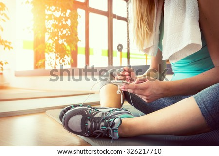 Attractive blond woman with smart phone, resting after gym workout - stock photo