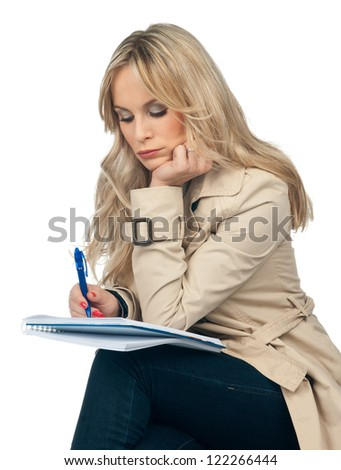 attractive blond woman writing in the notebook - stock photo