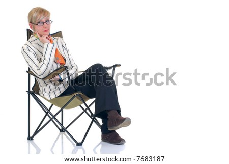 Attractive blond young businesswoman in director chair, pensive look.  White background, studio shot.