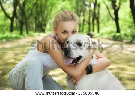 Attractive blond young girl playing with dog at the park