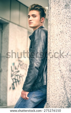 Attractive blond young man with leather jacket standing outside against pillar, looking down at camera - stock photo