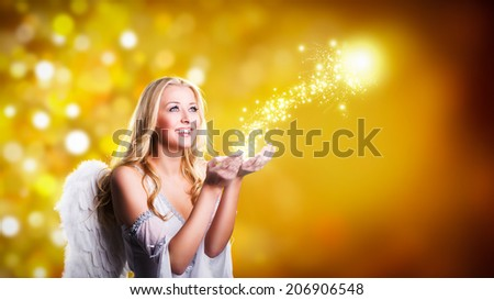 attractive blonde angel with christmas magic - stock photo