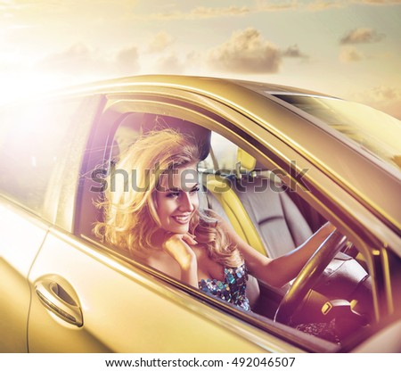 Attractive blonde beauty in an elegant car