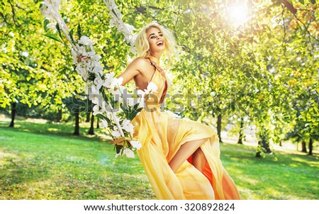 Attractive blonde beauty on a flower swing in a park - stock photo